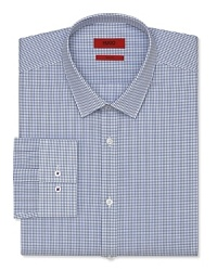 A slim fit HUGO dress shirt touts a plaid pattern and traditional barrel cuffs for streamlined office polish.