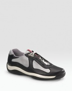 Lace-up sneaker with leather and mesh upper on a rubber sole. Padded insole Molded rubber bottom Imported