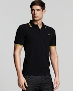 Widely known as the pioneer of Mod, British street fashion, Fred Perry polos have become an iconic fashion silhouette. A sporty polo with contrast double stripe trim and embroidered logo at left chest. Slim fit.
