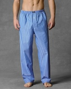 Woven cotton pajama pants with button fly and drawstring and elastic waist. Woven patch on front waistband. Blue, navy and white stripe.