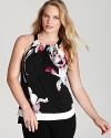 Winter florals bloom against a Tahari Woman Plus blouse, flaunting a chic halter neckline and tiered contrast trim for a modern feminine statement.
