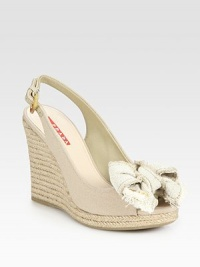 Canvas and espadrille wedge design with bow detail and an adjustable slingback. Espadrille wedge, 4 (100mm)Espadrille platform, ½ (15mm)Compares to a 3½ heel (90mm)Canvas upperLeather liningRubber solePadded insoleImportedOUR FIT MODEL RECOMMENDS ordering true size.